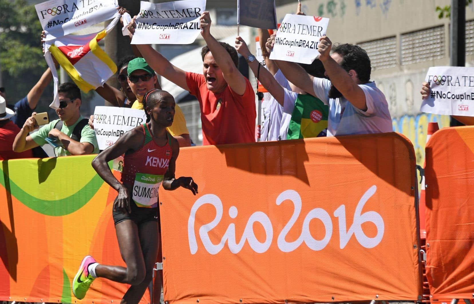 Jemima Jelagat Sumgong (Kenya) a couru devant des manifestants brandissant des pancartes «Fora Temer» le long du parcours dimanche, à Rio.