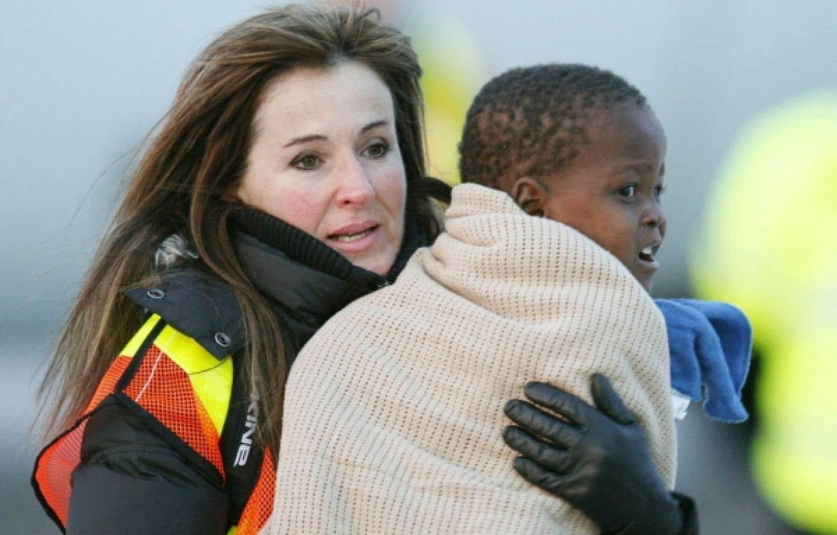 Une accompagnatrice porte dans ses bras l'un des 24 orphelins haïtiens arrivés hier à Ottawa.