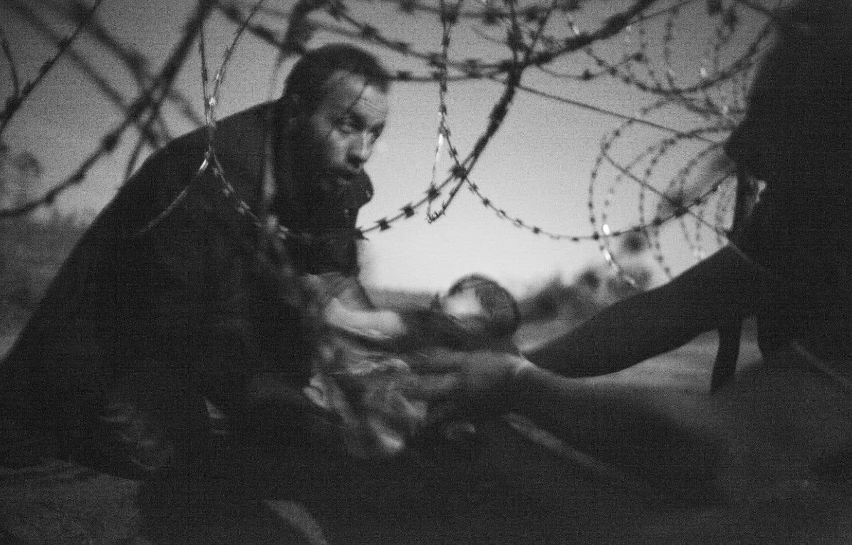 «Espoir d'une nouvelle vie», 28 août 2015, à la frontière serbo-hongroise, prix de la photo de l'année 2015. Un bébé est remis à travers des fils barbelés à un réfugié syrien parvenu à traverser la frontière séparant la Serbie de la Hongrie, près de Röszke.