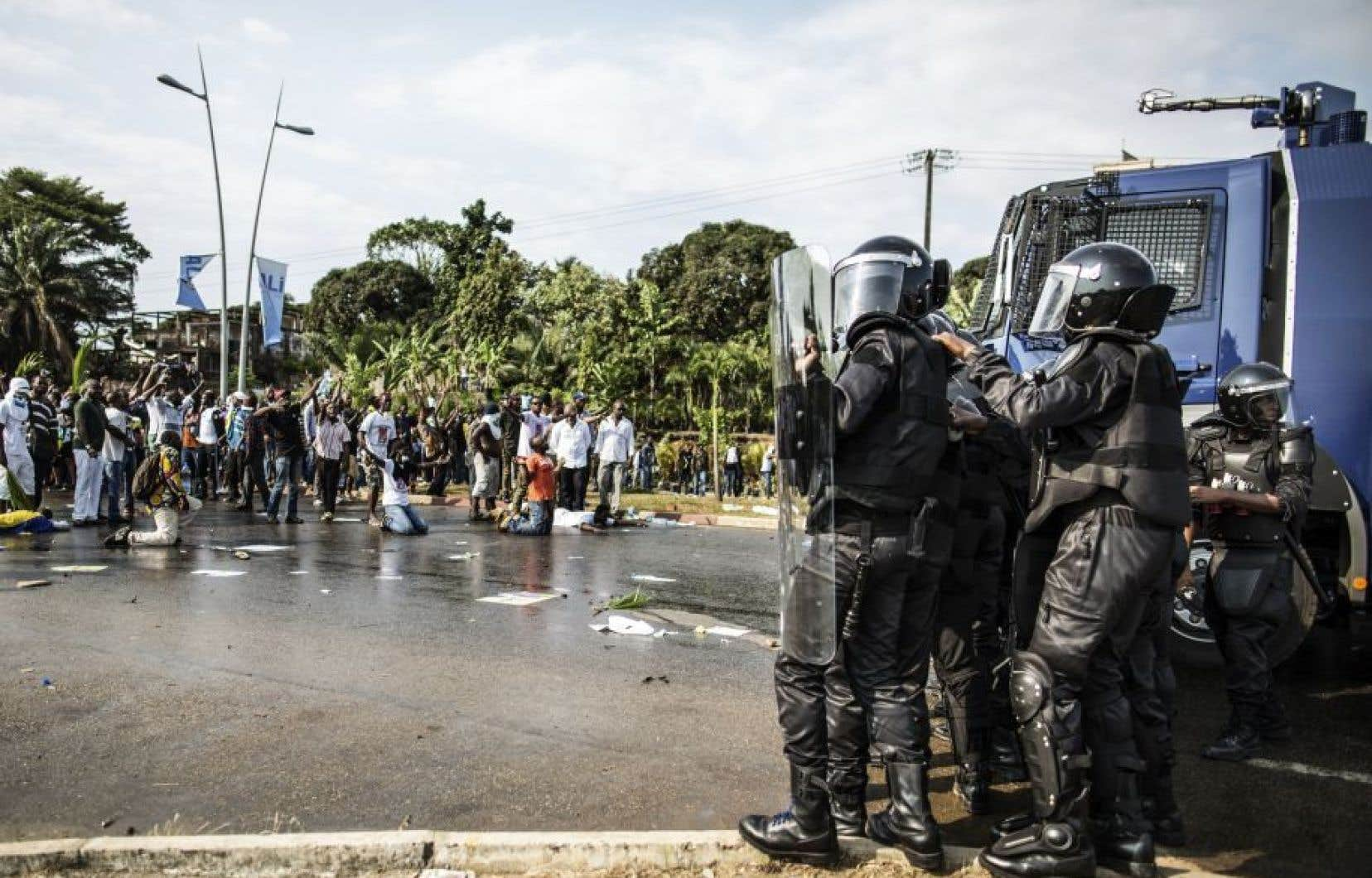 Des policiers de l'escouade antiémeute prennent position devant des partisans de Jean Ping à Libreville, mercredi.