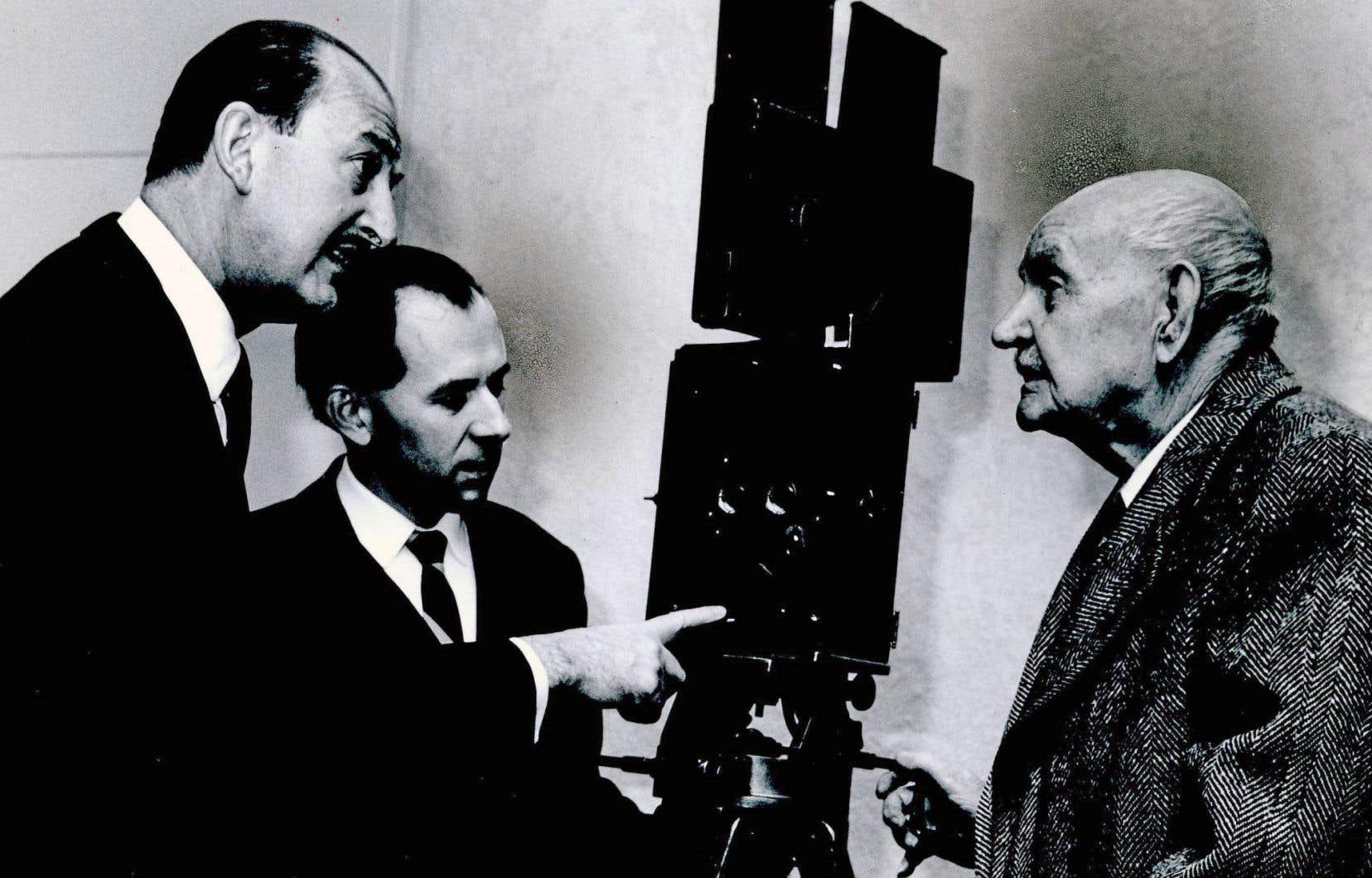 Léo-Ernest Ouimet, à droite, avec une caméra Pathé qu'il a utilisée à profusion, en compagnie du producteur Michel Costomet et de Guy-L. Côté, de la Cinémathèque québécoise.