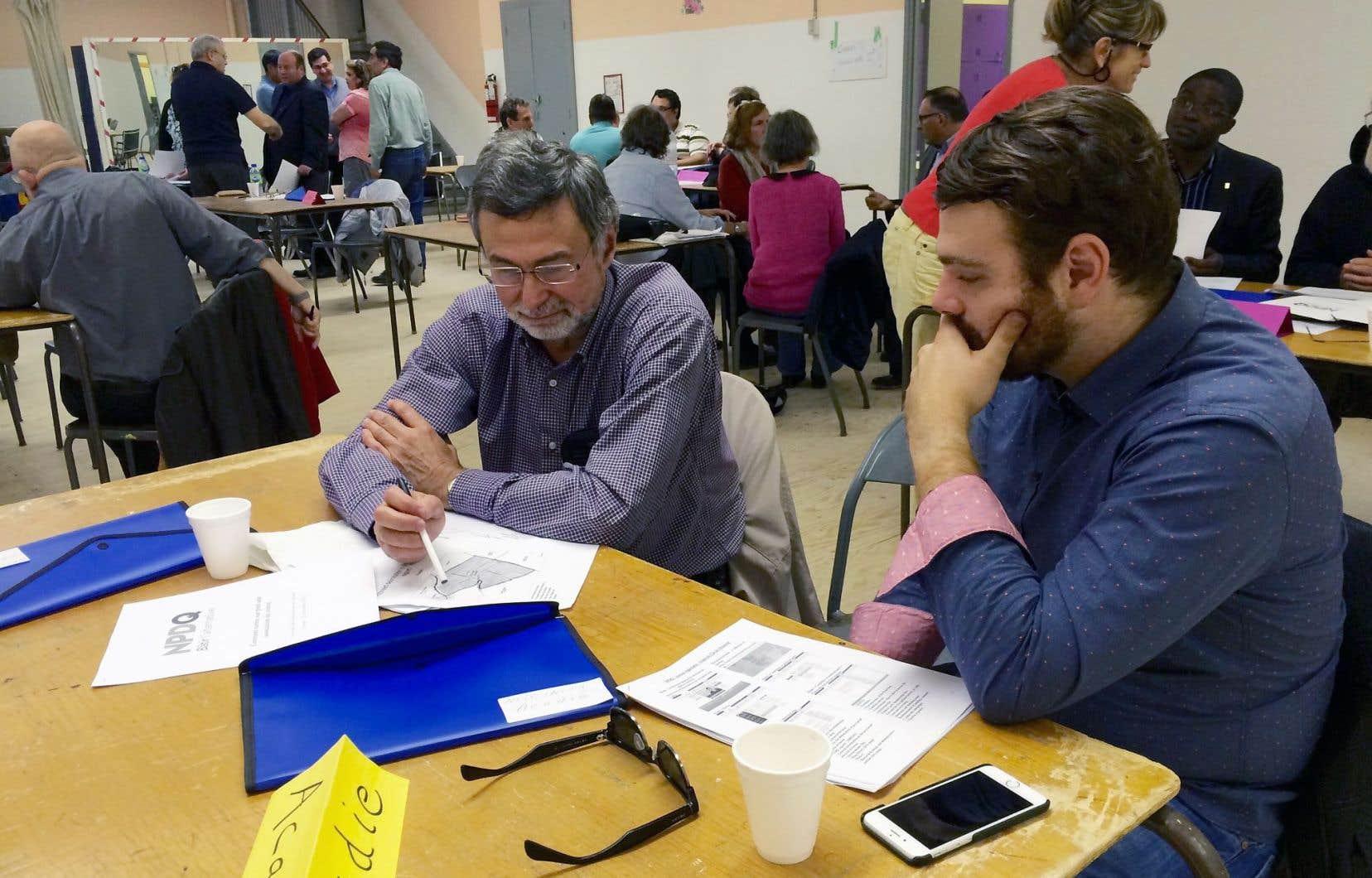 Deux militants du NPD-Q étudiaient la carte de la circonscription Acadie lors d'une discussion sur la manière de recruter des membres.
