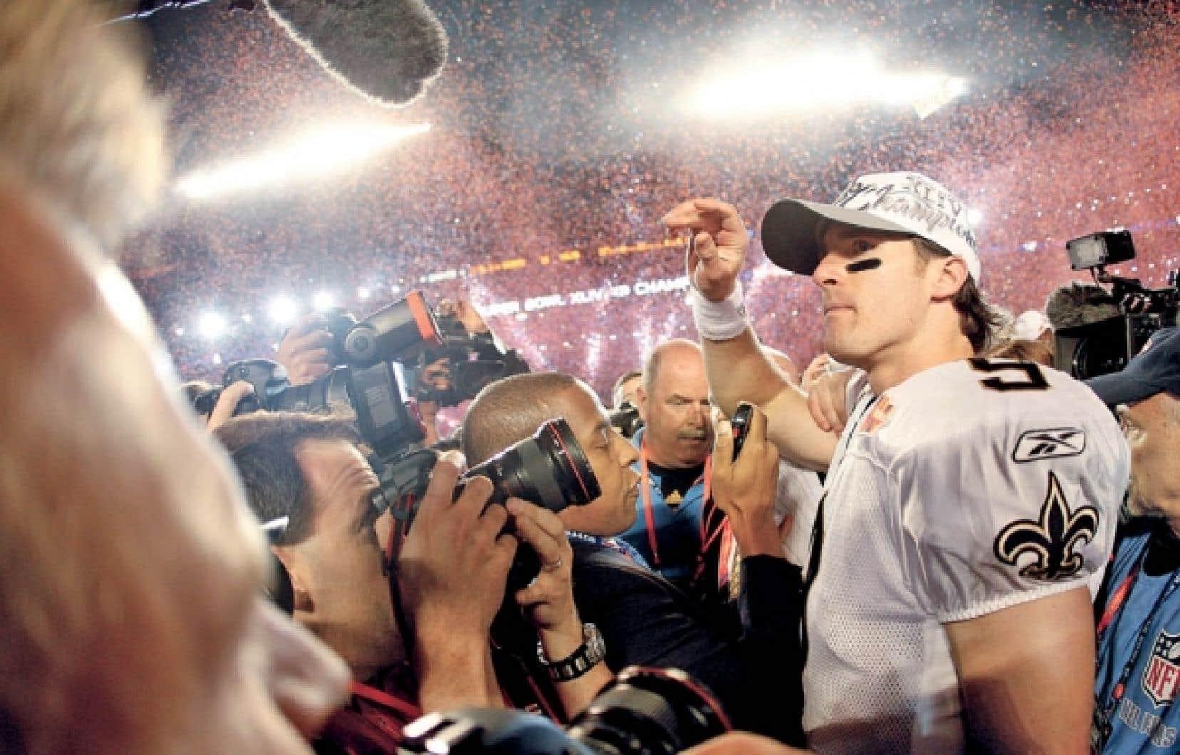 Le quart-arrière des Saints de La Nouvelle-Orléans, Drew Brees, entouré de photographes après la victoire de son équipe, hier.