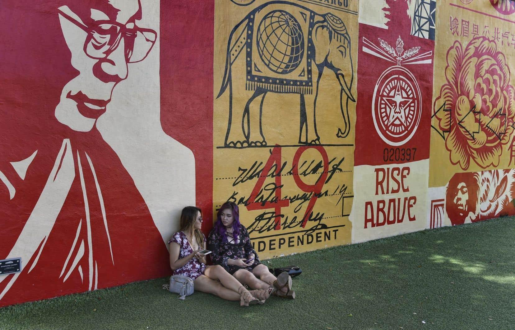 Deux jeunes touristes venues de Fort Lauderdale discutent, assises devant une murale de Shepard Fairey.