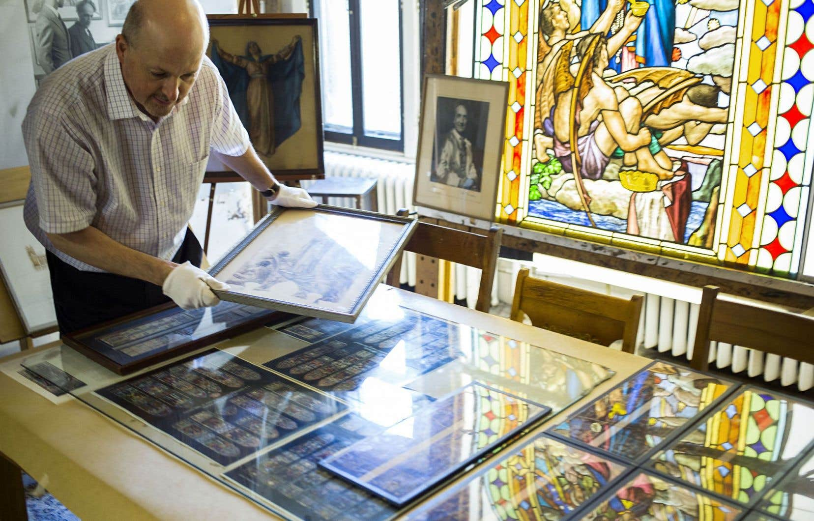 Le directeur du musée Dufresne-Nincheri, Paul Labonne, examine des maquettes dans le studio de l'artiste. À droite se trouve le vitrail commandé dans les années 1960 par une paroisse d'Hochelaga. Alors que l'église compte 14 verrières réalisées par Nincheri, celle-ci, non payée, n'a jamais été livrée…