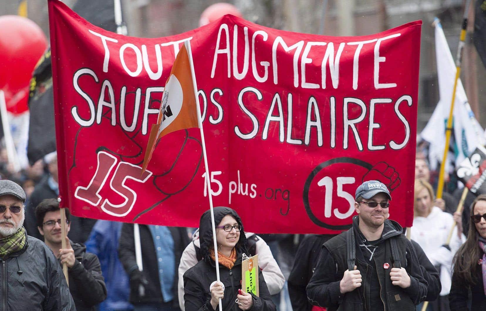 Une affiche appelant à la hausse du salaire minimum à 15$ brandie lors d'une manifestation, le 1ermai dernier