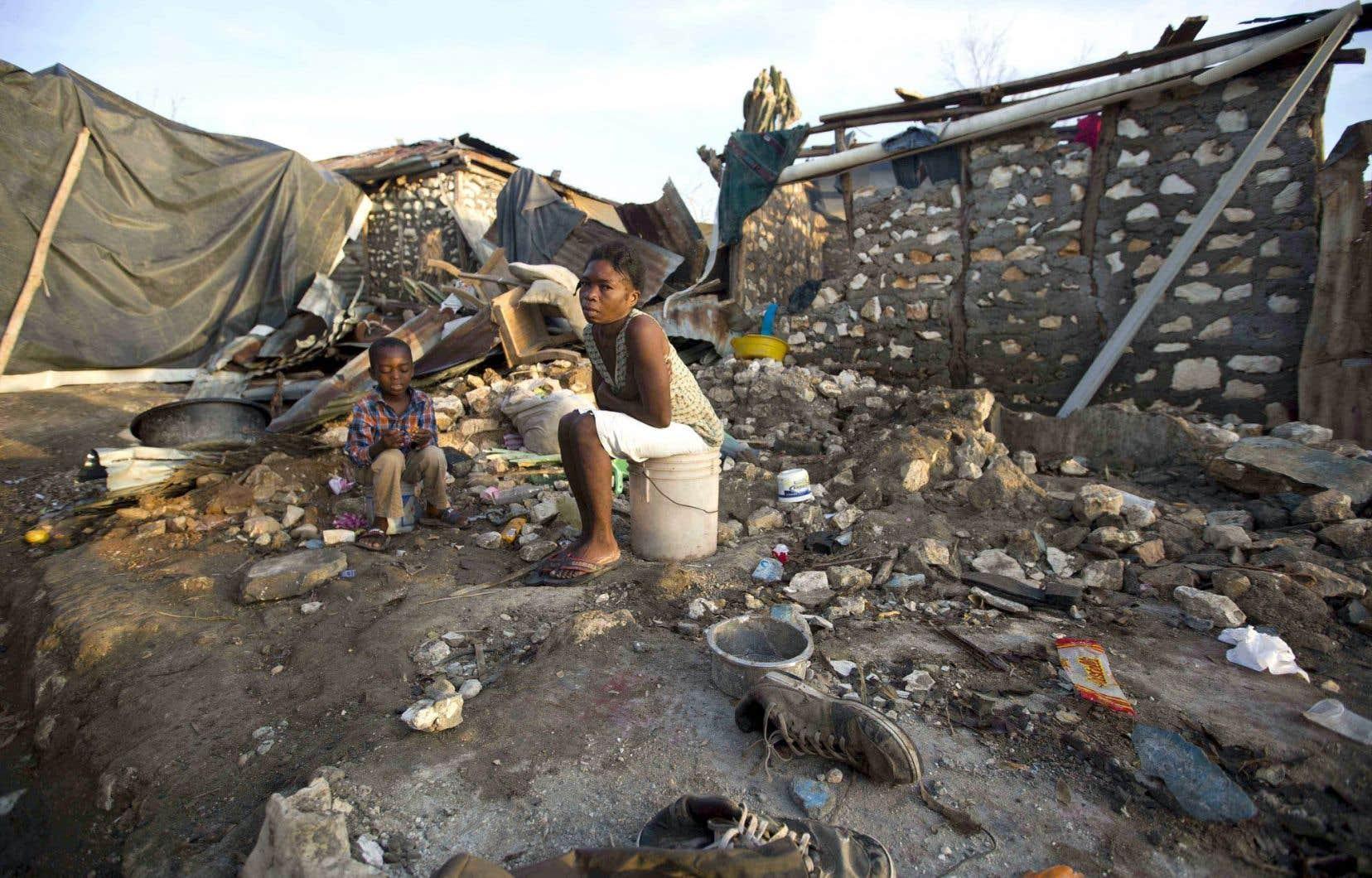Une femme et son fils occupent ce qu'il reste de leur demeure détruite par l'ouragan dans la ville côtière de Jérémie.