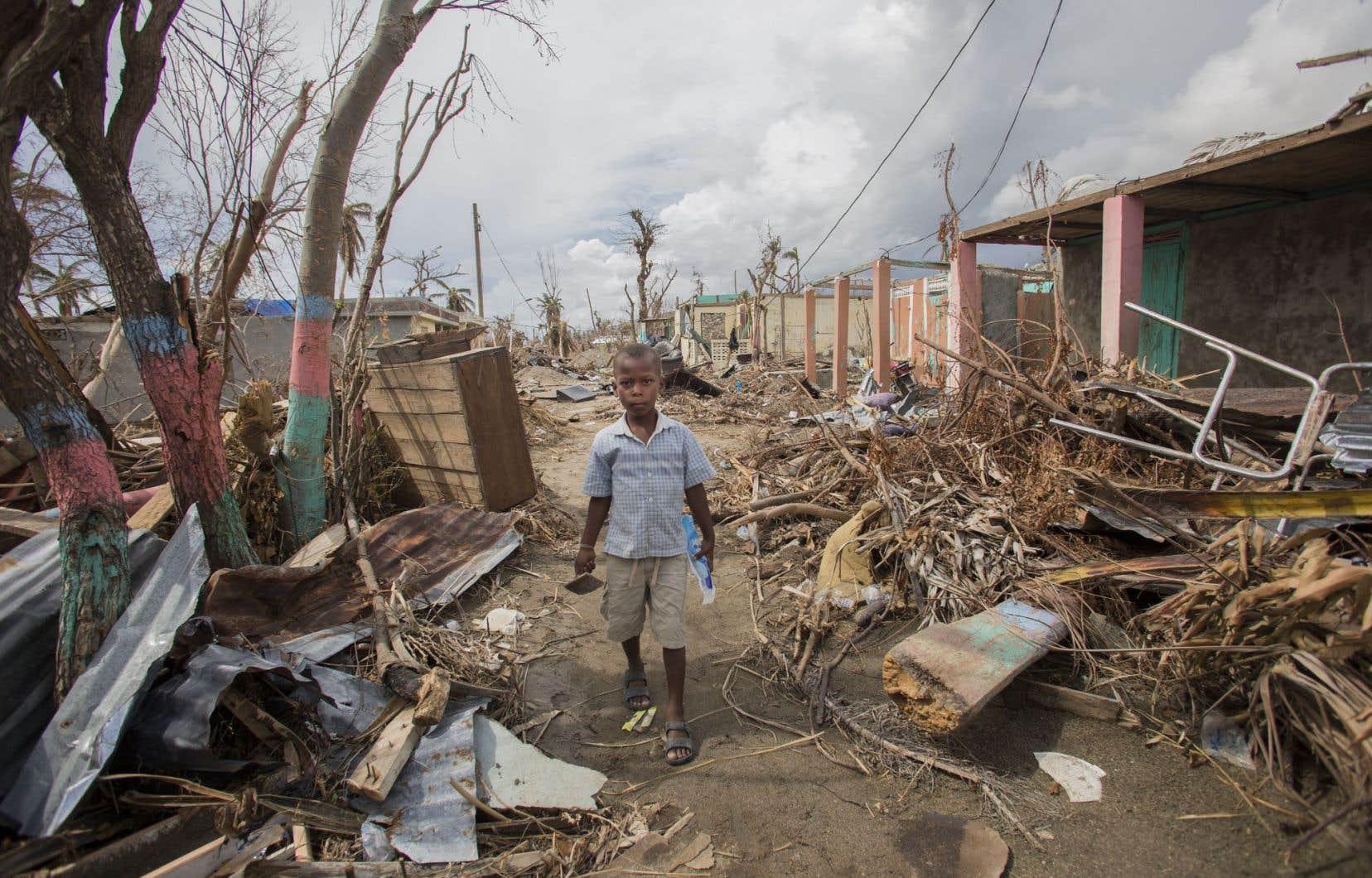 Cet enfant se fraie un chemin au milieu des débris que la mer a transportés dans les rues du village de Roche-à-Bateau.