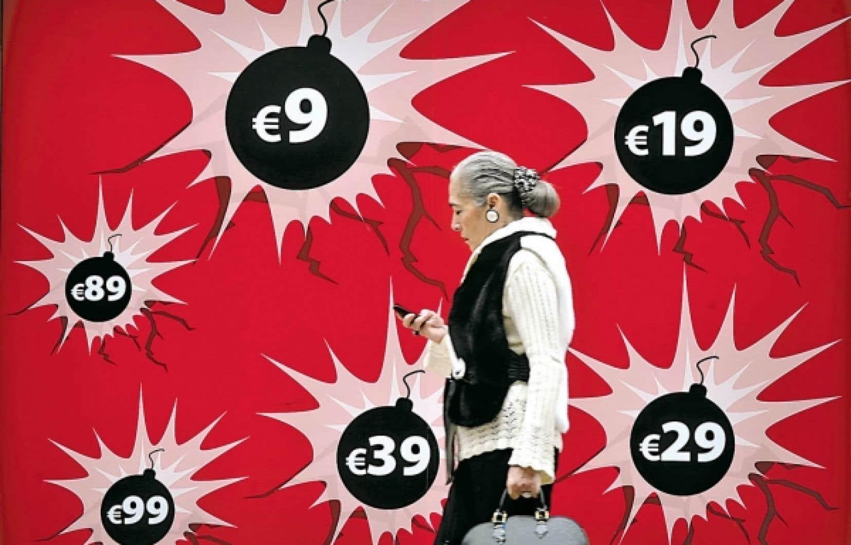 Une femme marche devant la vitrine d'une boutique à Athènes. Cette semaine, l'Europe a pressé la Grèce de prendre en main ses dettes et son déficit.