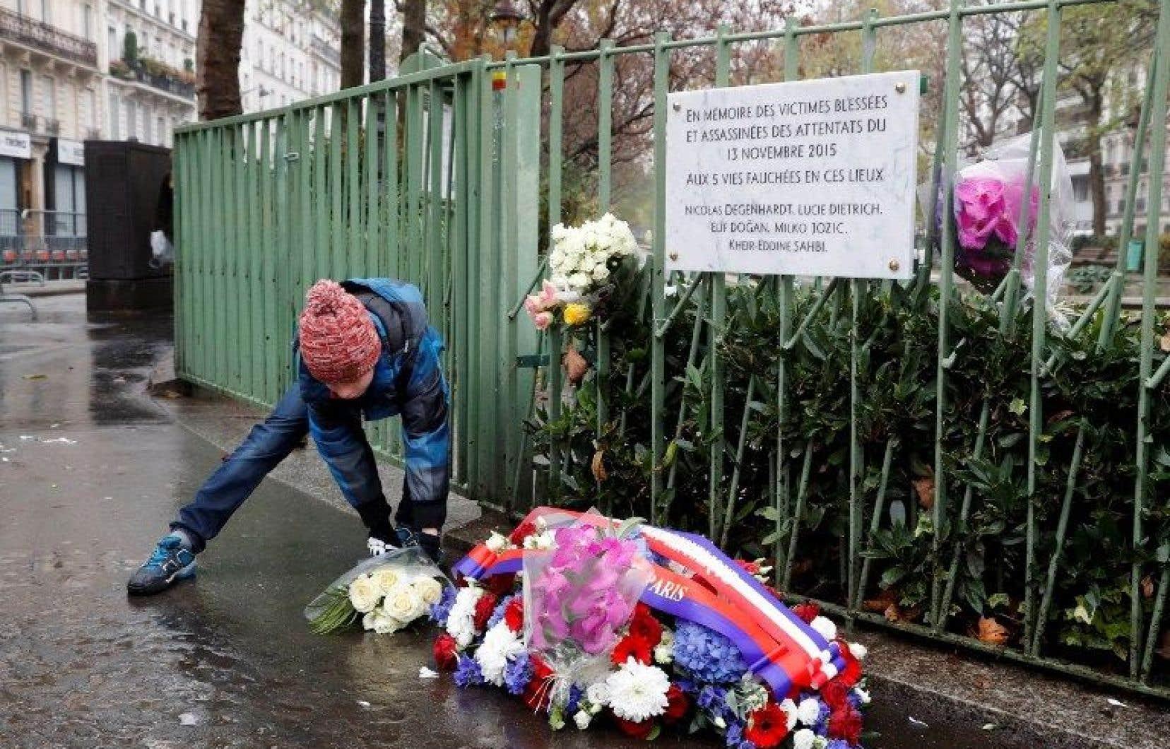Un enfant dépose des fleurs devant une plaque en mémoire aux victimes qui ont perdu la vie le 13 novembre 2015, proche du Café Bonne Bière à Paris.