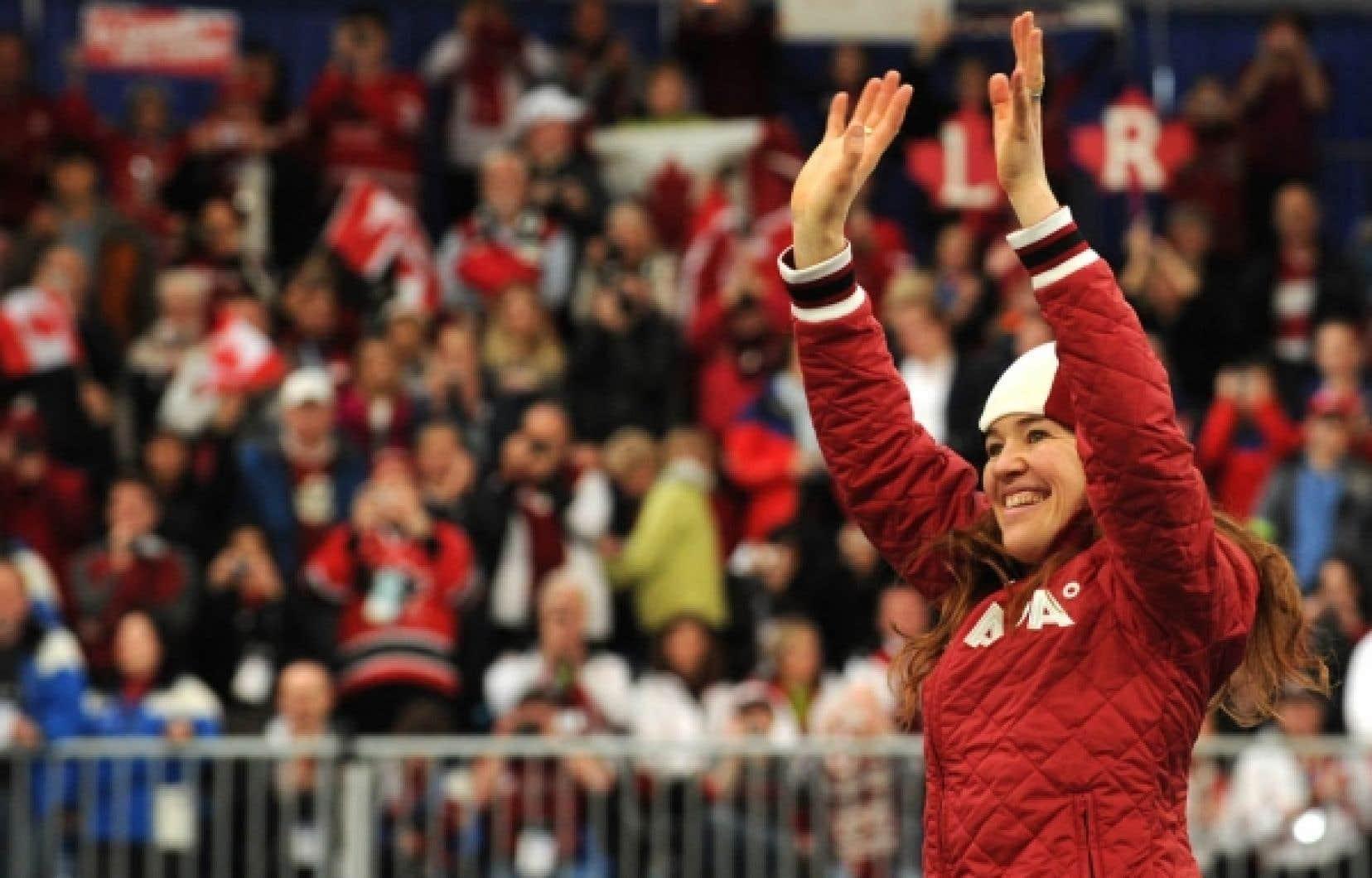 Clara Hughes salue la foule avant de monter sur le podium. L'athlète de 37 ans a participé à deux Jeux d'été (à titre de cycliste) et trois Jeux d'hiver.