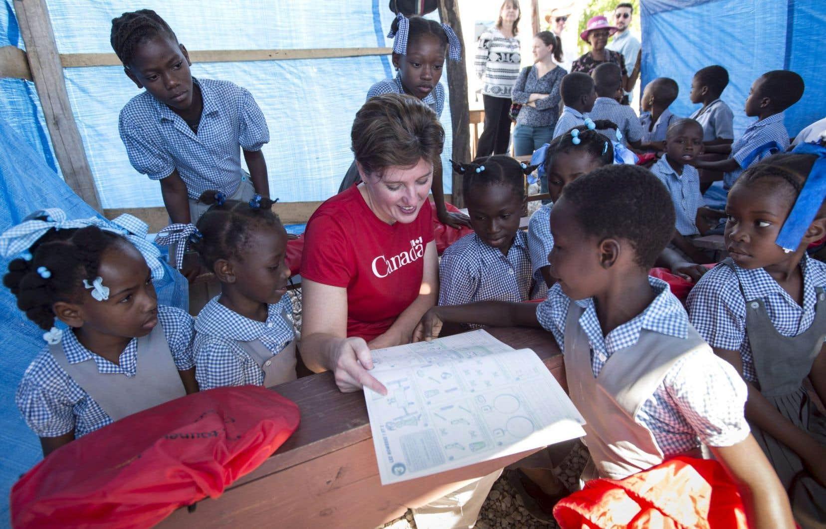 La ministre du Développement international, Marie-Claude Bibeau, a fait la lecture à des écolières de l'école du camp Perrin, en Haïti.