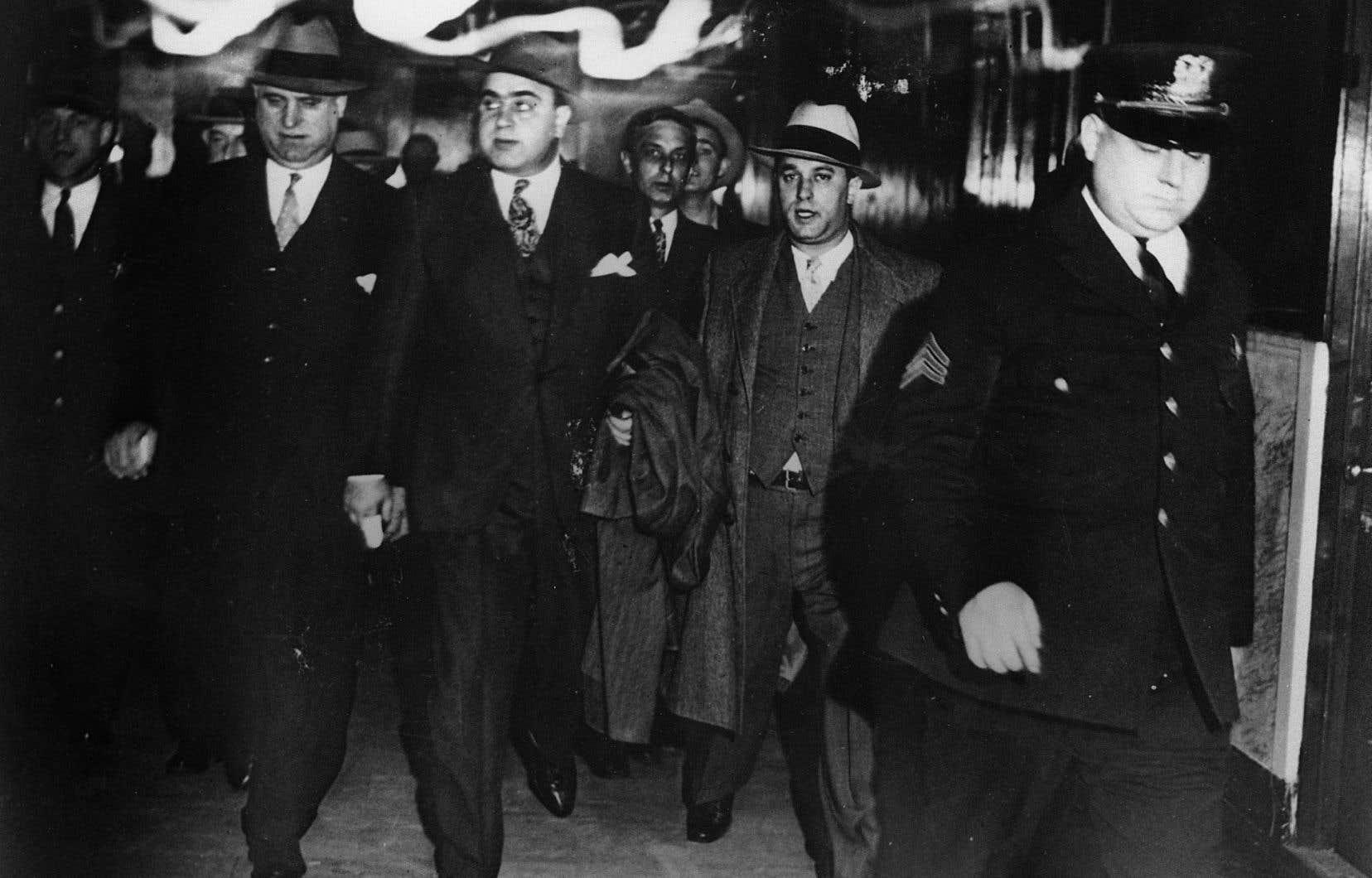 Al Capone (au centre), se faisant escorter hors du tribunal pendant son procès pour évasion fiscale.
