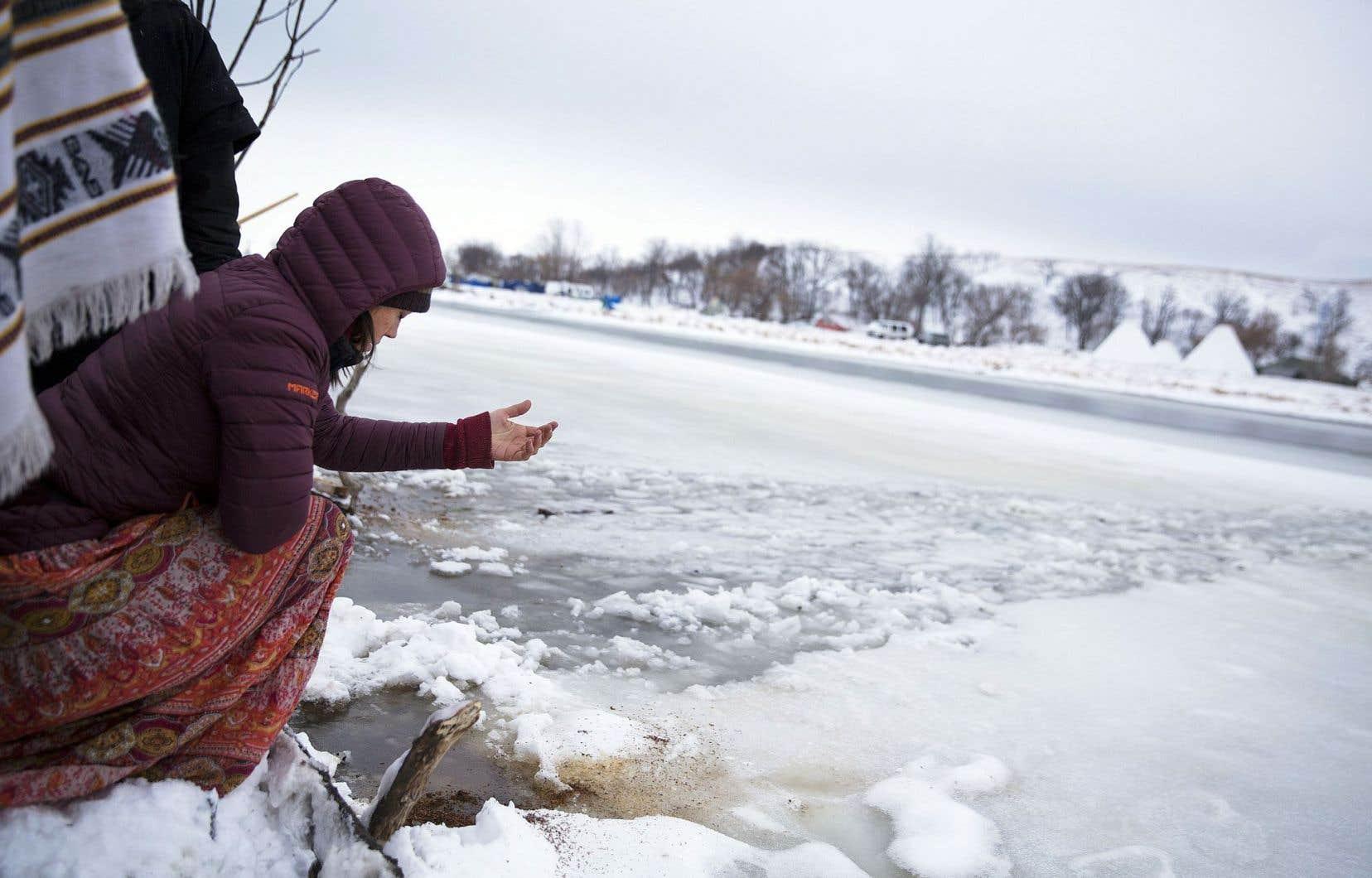 Megan Toben jette du tabac sur les rives de la rivière Cannonball, dans le Dakota du Nord, aux États-Unis, durant une cérémonie autochtone de l'eau.