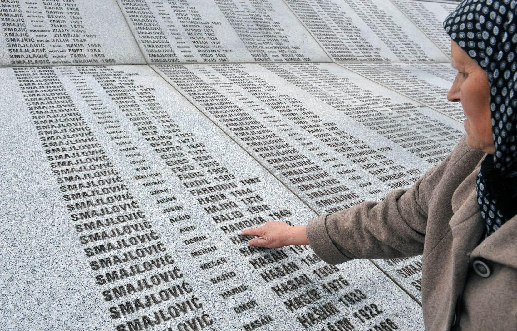 Bida Smaljovic, survivante du massacre de Srebrenica, pointe le nom de son mari au milieu des noms des victimes sur un mémorial à Potocari, en Bosnie-Herzégovine.