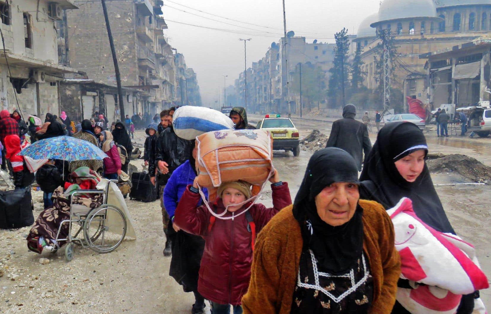 <p>Dans le quartier de Fardos, à Alep, des hommes, des femmes et des enfants fuient sous lapluie fine.</p>