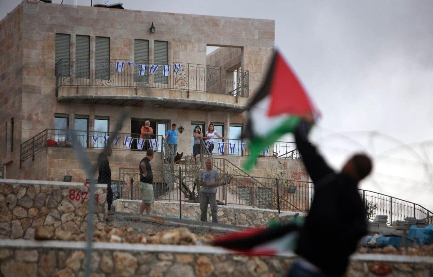 Des Israéliens de la colonie Har Gilo, près de Bethléem, observent un Palestinien brandir le drapeau national pour protester contre la construction d'un mur, en 2010.