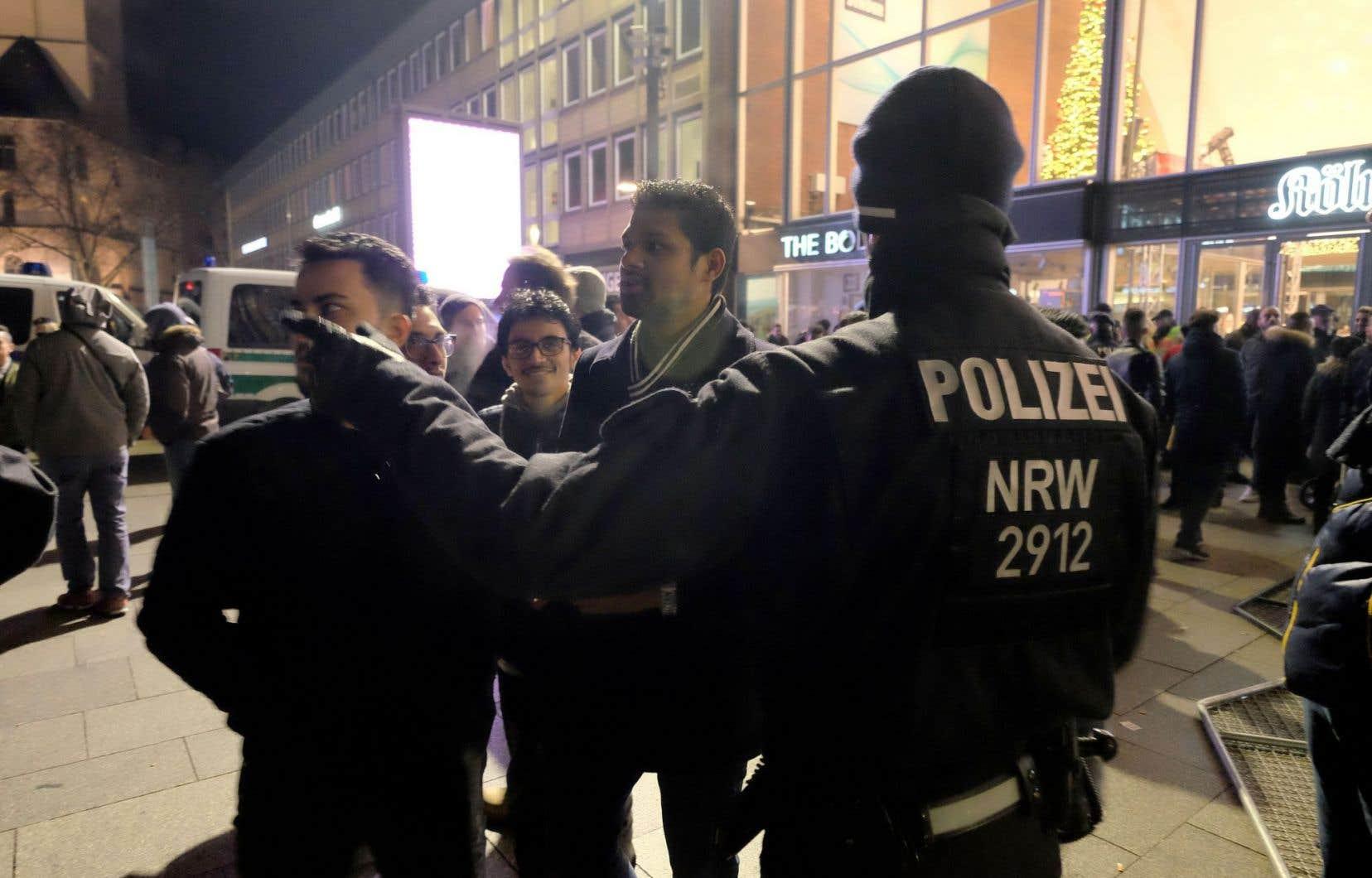Un policier interpelle des passants lors des festivités du Nouvel An à Cologne.
