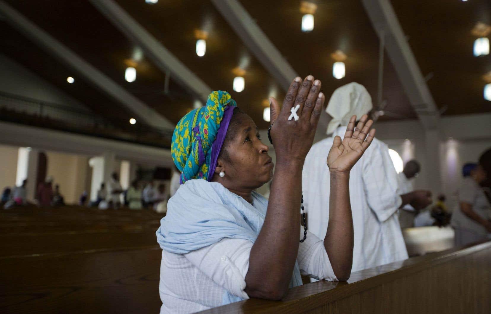 Une femme s'est rendue à une messe commémorative rendant hommage aux disparus, jeudi, à Port-au-Prince.