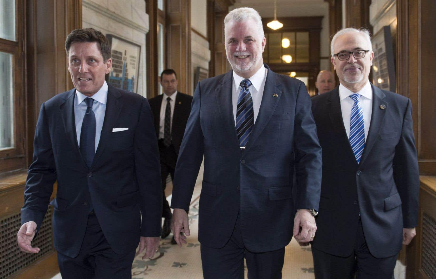 Le premier ministre du Québec, Philippe Couillard, est entouré du nouveau président du Conseil du trésor, Pierre Moreau (à gauche), et du ministre québécois des Finances, Carlos Leitão (à droite).