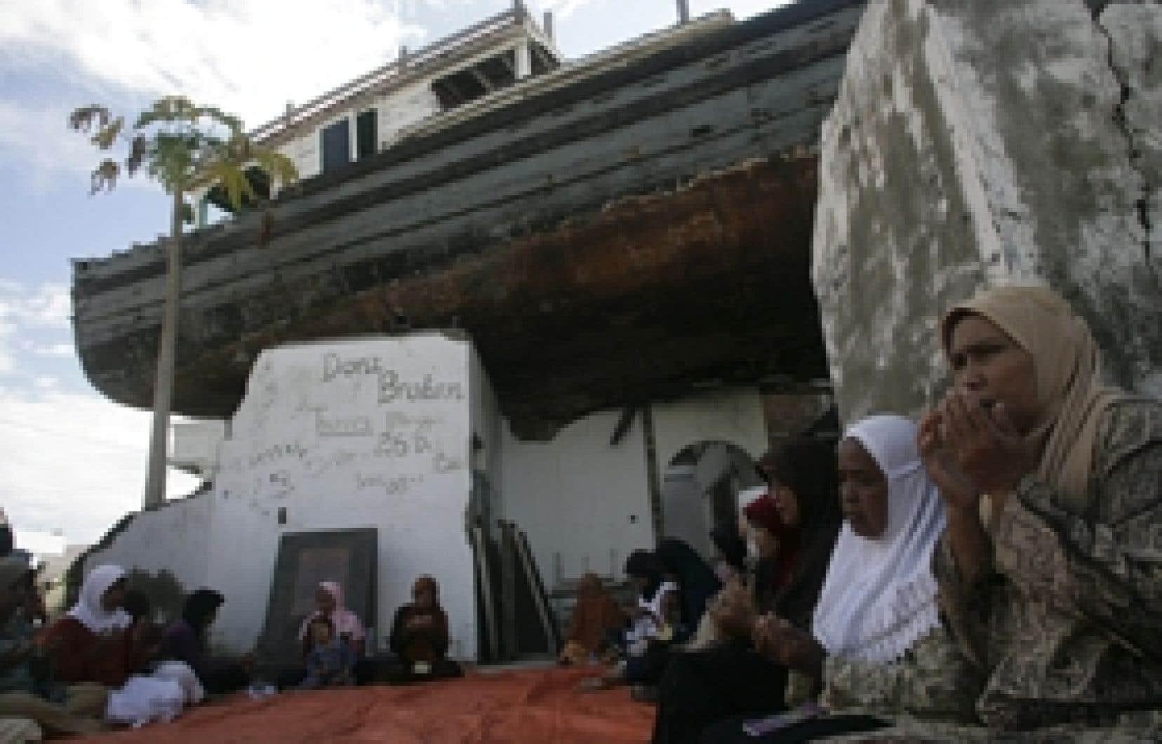 Des femmes prient sous un bateau de bois qui a été soulevé par le tsunami, le 26 décembre 2004.