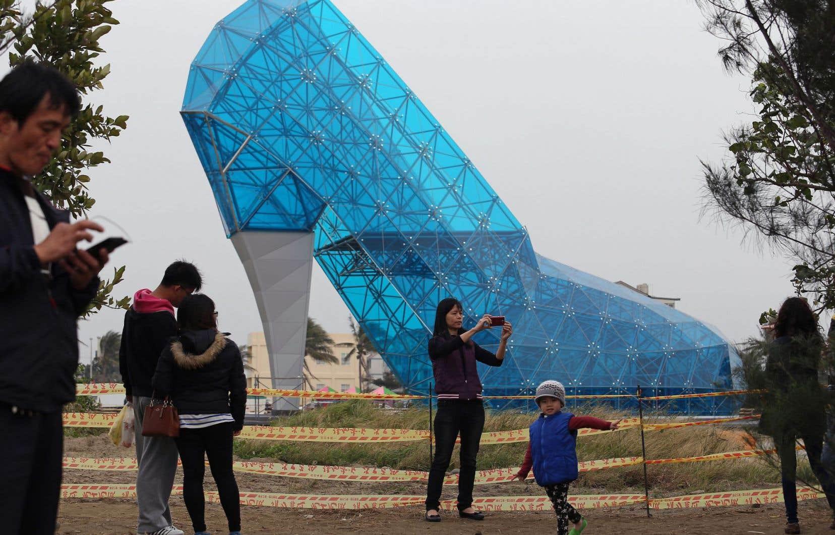 Des touristes devant une église en forme de... soulier, à Chiayi City. La «bâtisse» fait 55 pieds de hauteur sur 36 de largeur. Le public peut voir l'extérieur jusqu'à ce qu'elle soit officiellement ouverte en février2018, avant la Nouvelle Année lunaire.