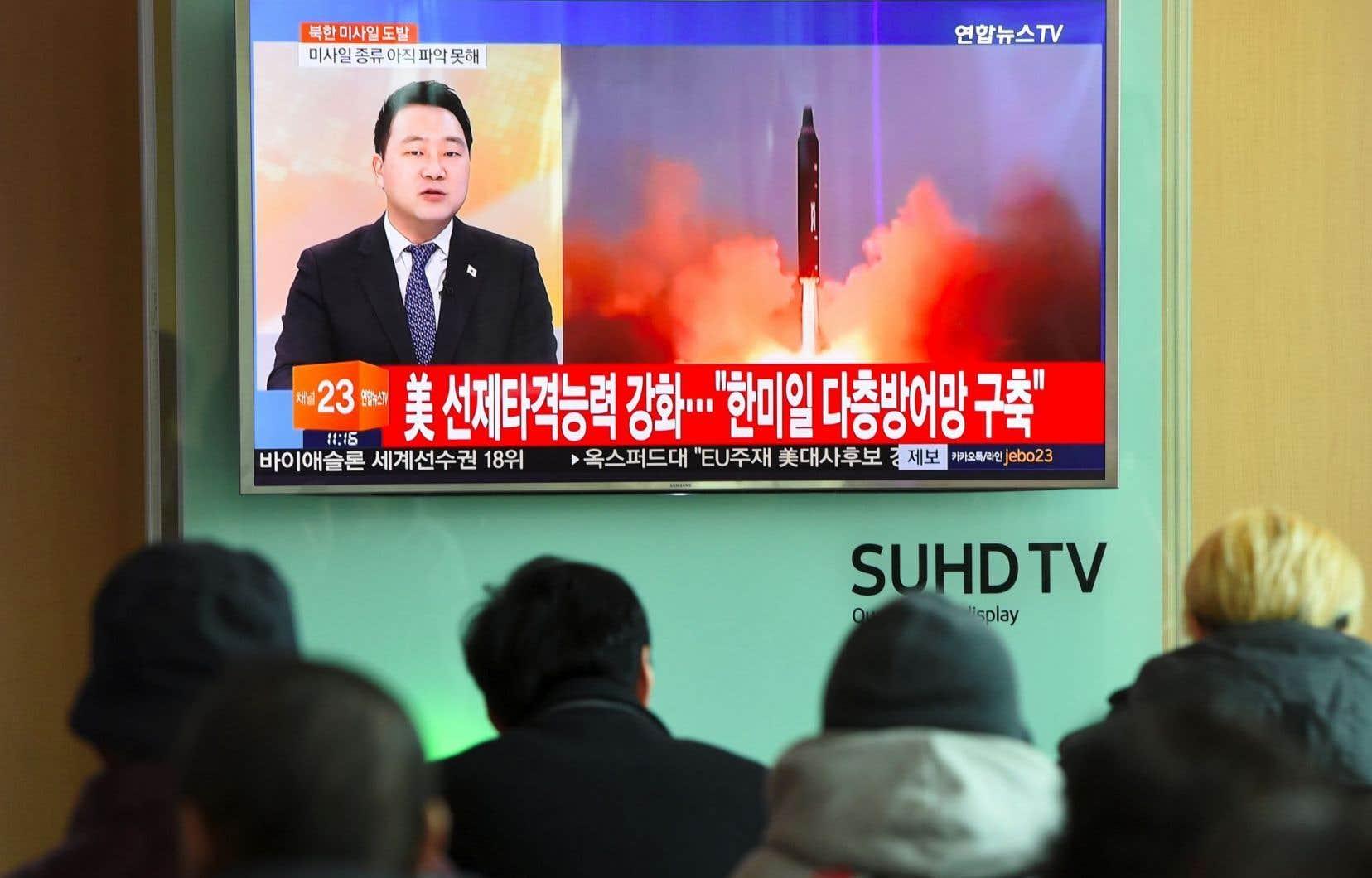 Des Sud-Coréens attroupés dans une gare de Séoul regardent des images du lancement de missile par la Corée du Nord.