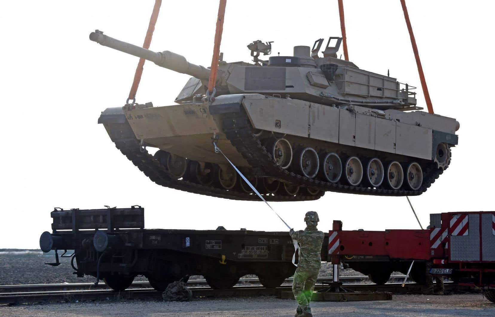 Un soldat américain aide au déchargement d'un char d'assaut sur une base militaire en Roumanie.