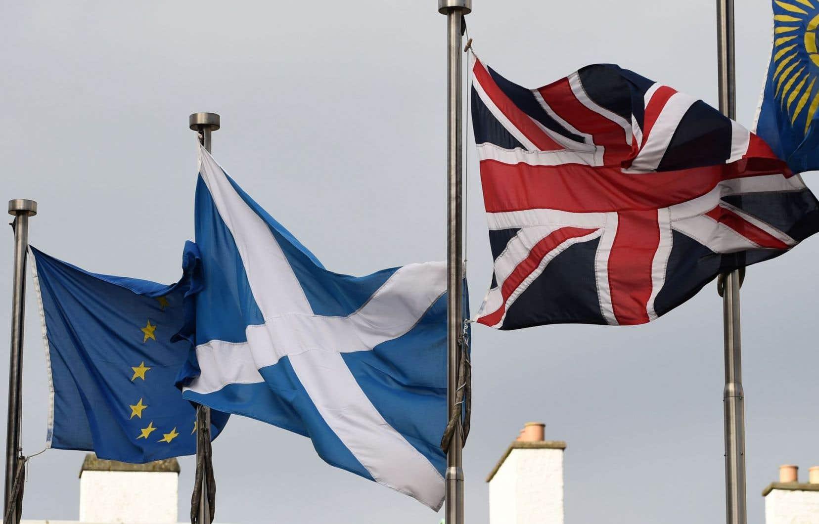 Le drapeau écossais bat au vent entre ceux de l'Union européenne et du Royaume-Uni.