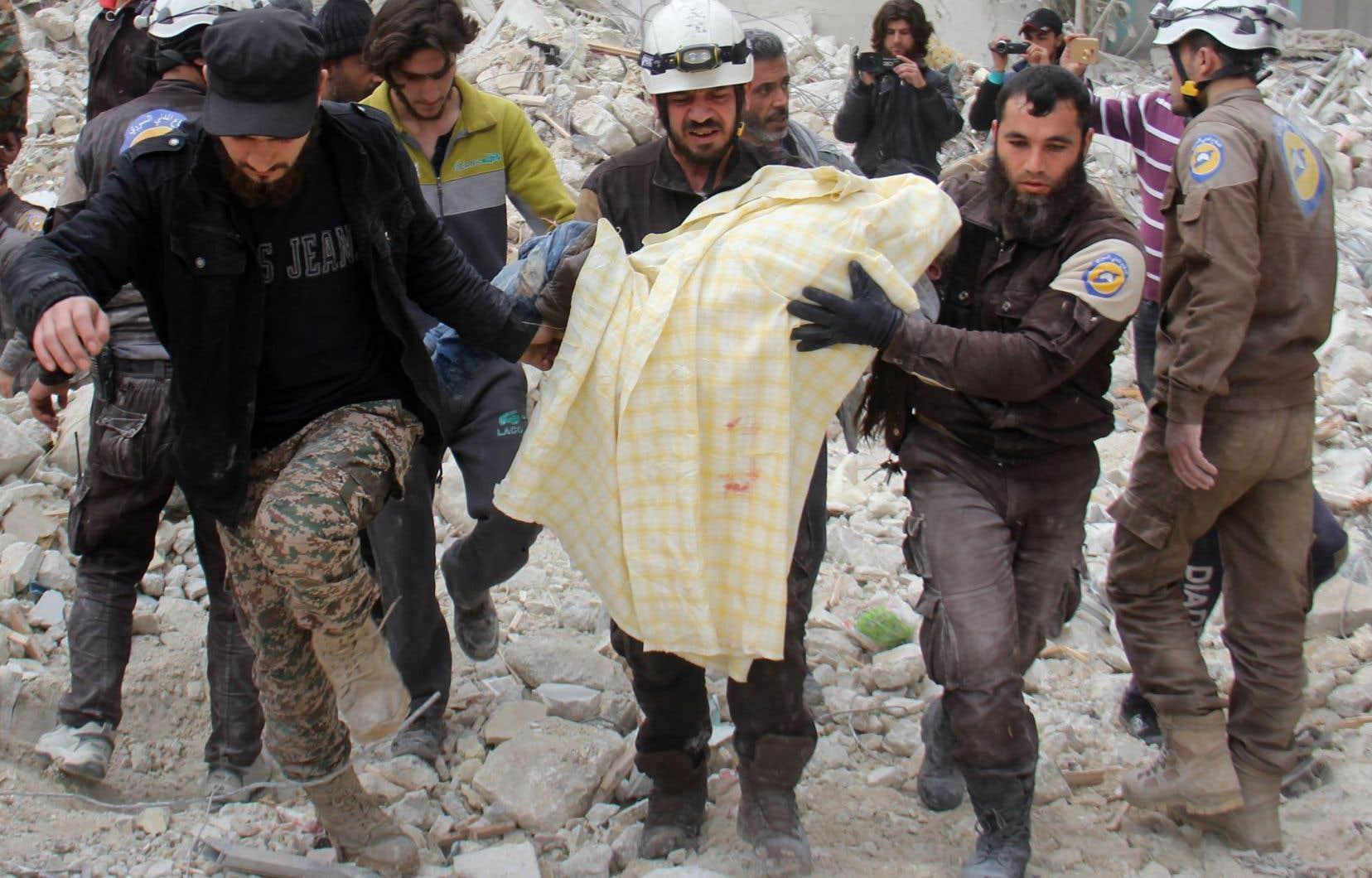 Des membres des Casques blancs retirent une victime des décombres d'un bâtiment détruit à la suite d'une attaque aérienne dans la ville d'Idlib, le 15 mars.