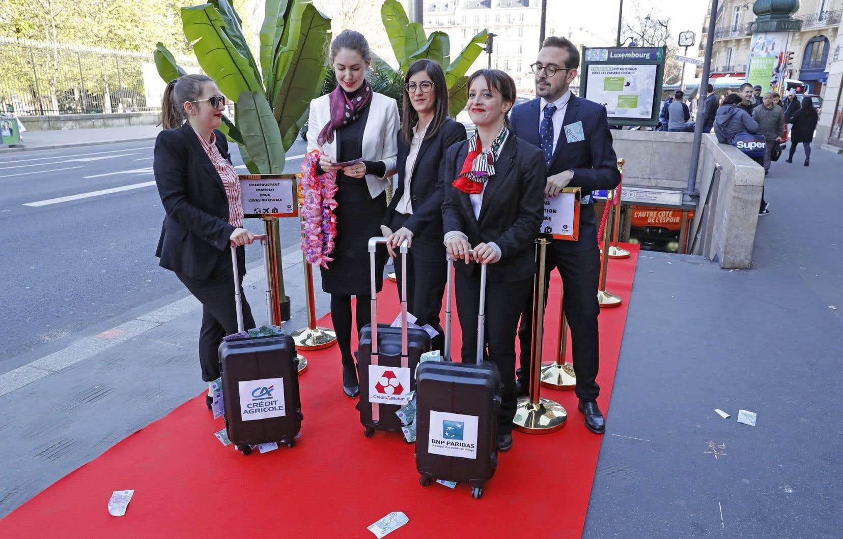 De faux banquiers de l'ONG se sont avancés sur un tapis rouge comme pour prendre l'avion avec des mallettes portant les noms de grandes banques françaises.