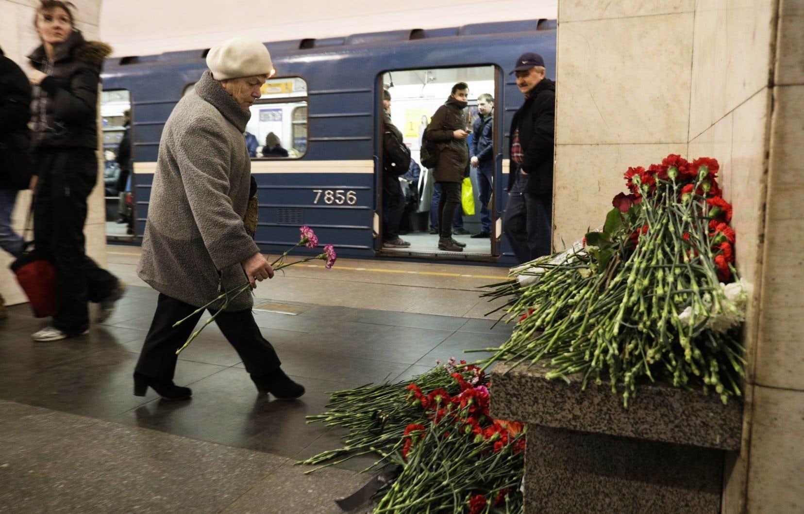 Une femme dépose des fleurs dans un mémorial symbolique à la station de métro Tekhnologichesky Institute à Saint-Pétersbourg, en Russie.