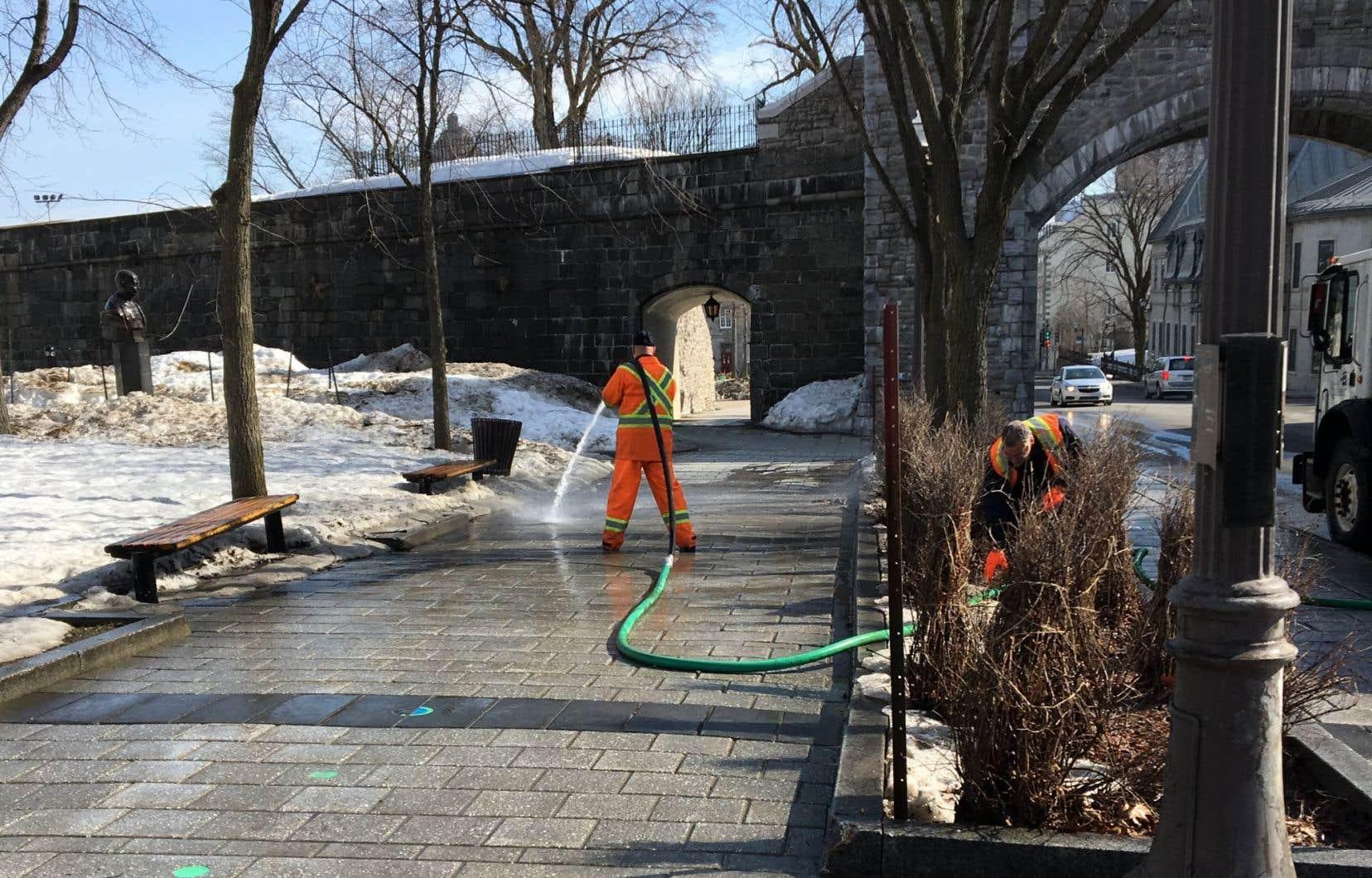 Un employé de la Ville de Québec arrose à grande eau le trottoir de la Grande Allée, près de la porte Saint-Louis, à Québec.