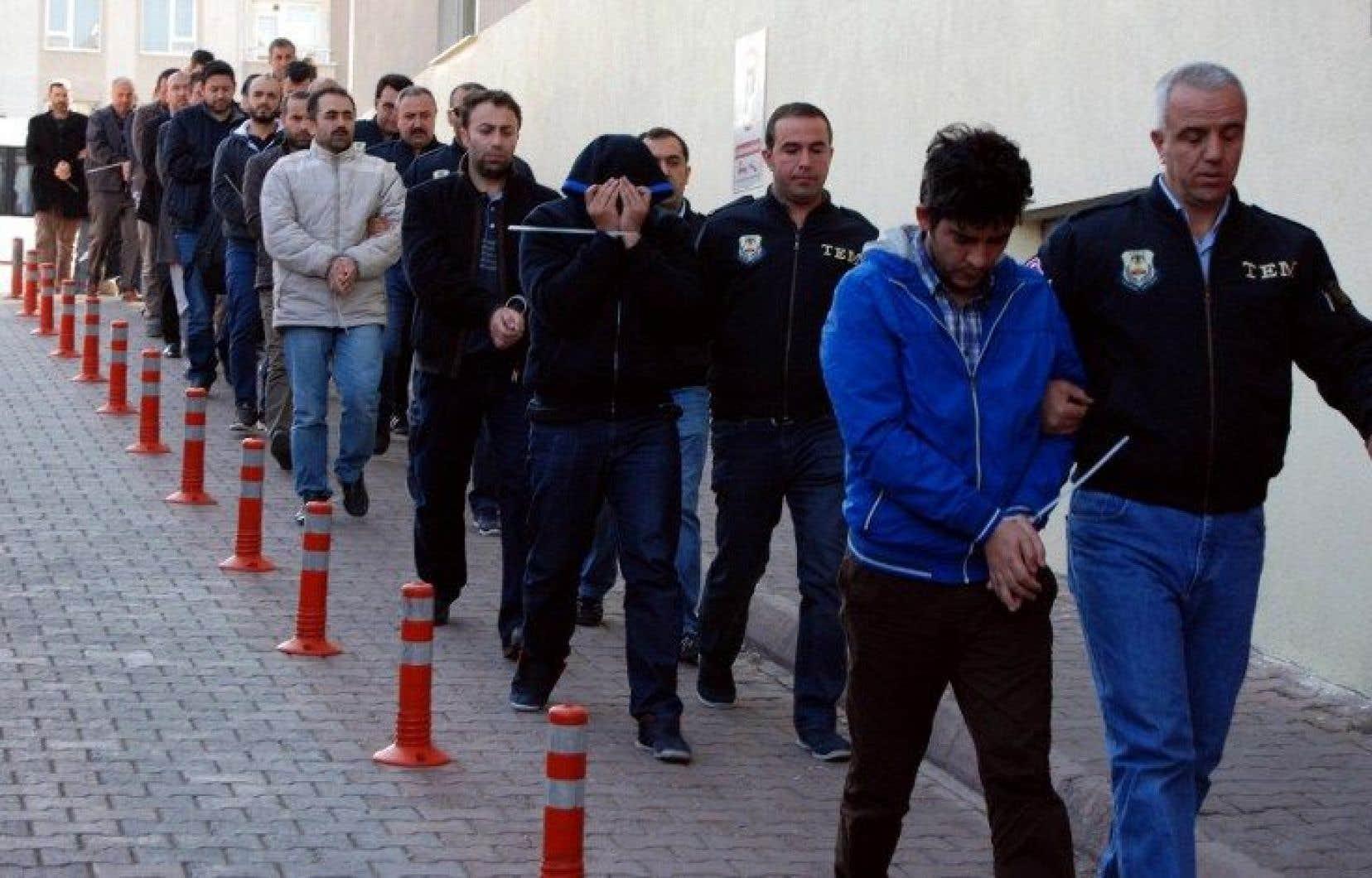 Des policiers turcs escortent des personnes qui ont été arrêtées mercredi.