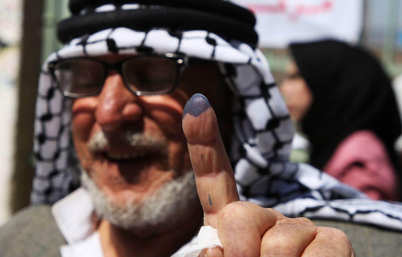 Un Palestinien exhibe son doigt taché d'encre, indiquant qu'il a voté.