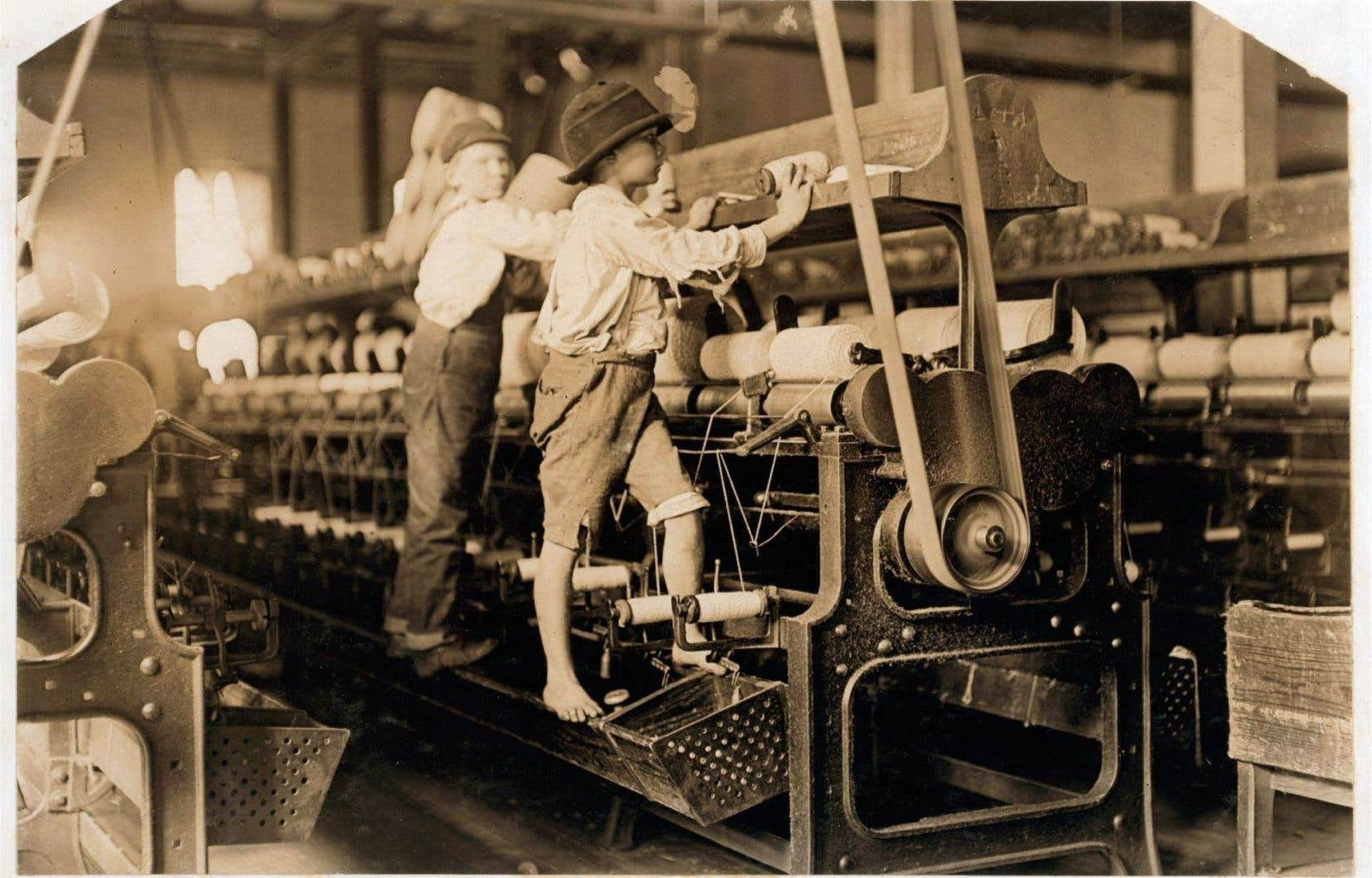 <p>Géorgie, 1909: deux enfants changent les bobines de fil d'une machine à tisser dans une usine de la petite ville de Macon sous le regard du photographe américain Lewis W. Hine.</p>