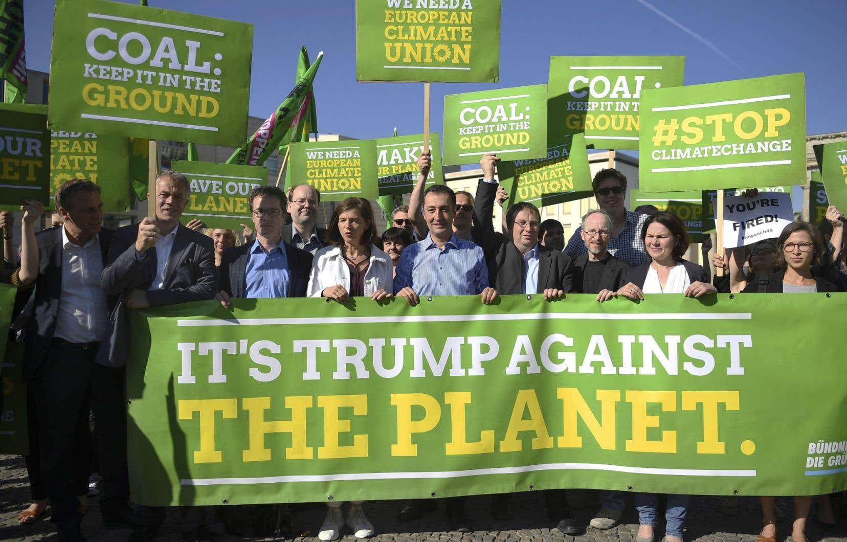Devant l'ambassade des États-Unis à Berlin, en Allemagne, des manifestants, dont des candidats du Parti vert, ont protesté vendredi contre la décision du président Donald Trump de se retirer de l'Accord de Paris. «C'est Trump contre la planète», peut-on lire sur la bannière.