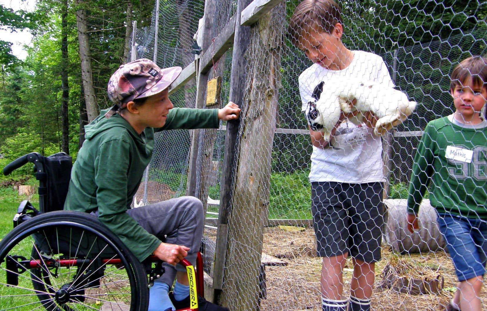 Roméo présente un des lapins du clapier à son ami Elyjah, 13ans, un Enfant Gioia. L'organisation permet à des enfants atteints de maladies incurables ou orphelines d'avoir accès à la nature et d'être moins surprotégés.