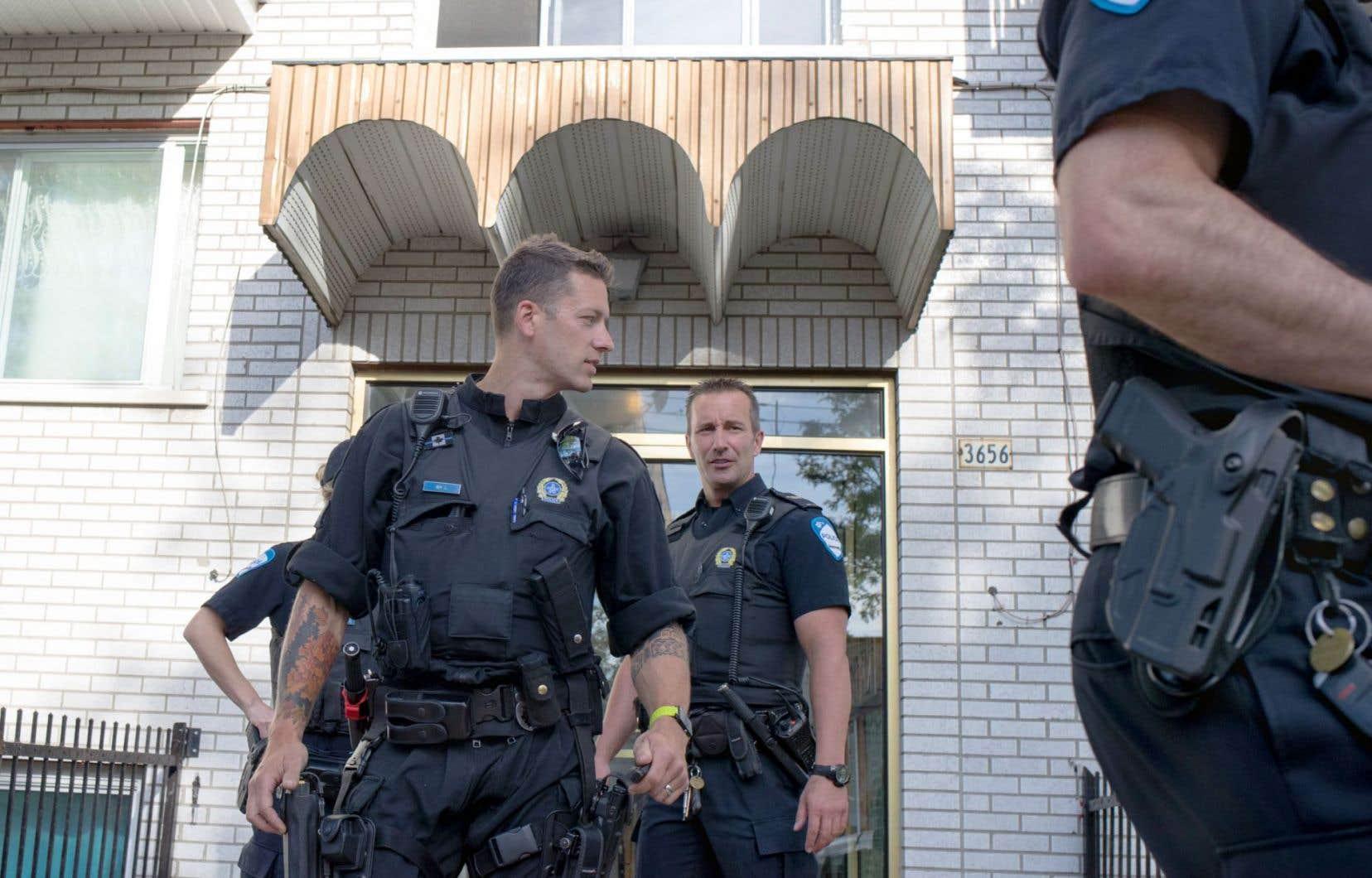 Des policiers devant l'édifice à logements dans le quartier Saint-Michel, à Montréal, où réside le suspect de l'agression perpétrée dans un aéroport à Flint, au Michigan