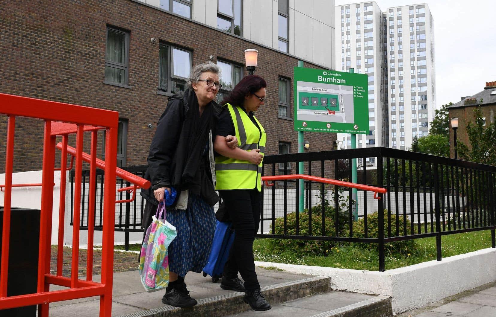 Une résidente (à gauche) est évacuaée de l'immeuble résidentiel Burnham Tower sur le domaine Chalcots dans le nord de Londres.