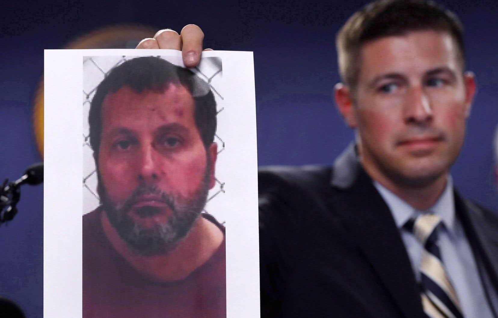 Un agent du FBi brandit une photo d'Amor Ftouhi, soupçonné d'avoir poignardé un policier à l'aéroport de Flint.