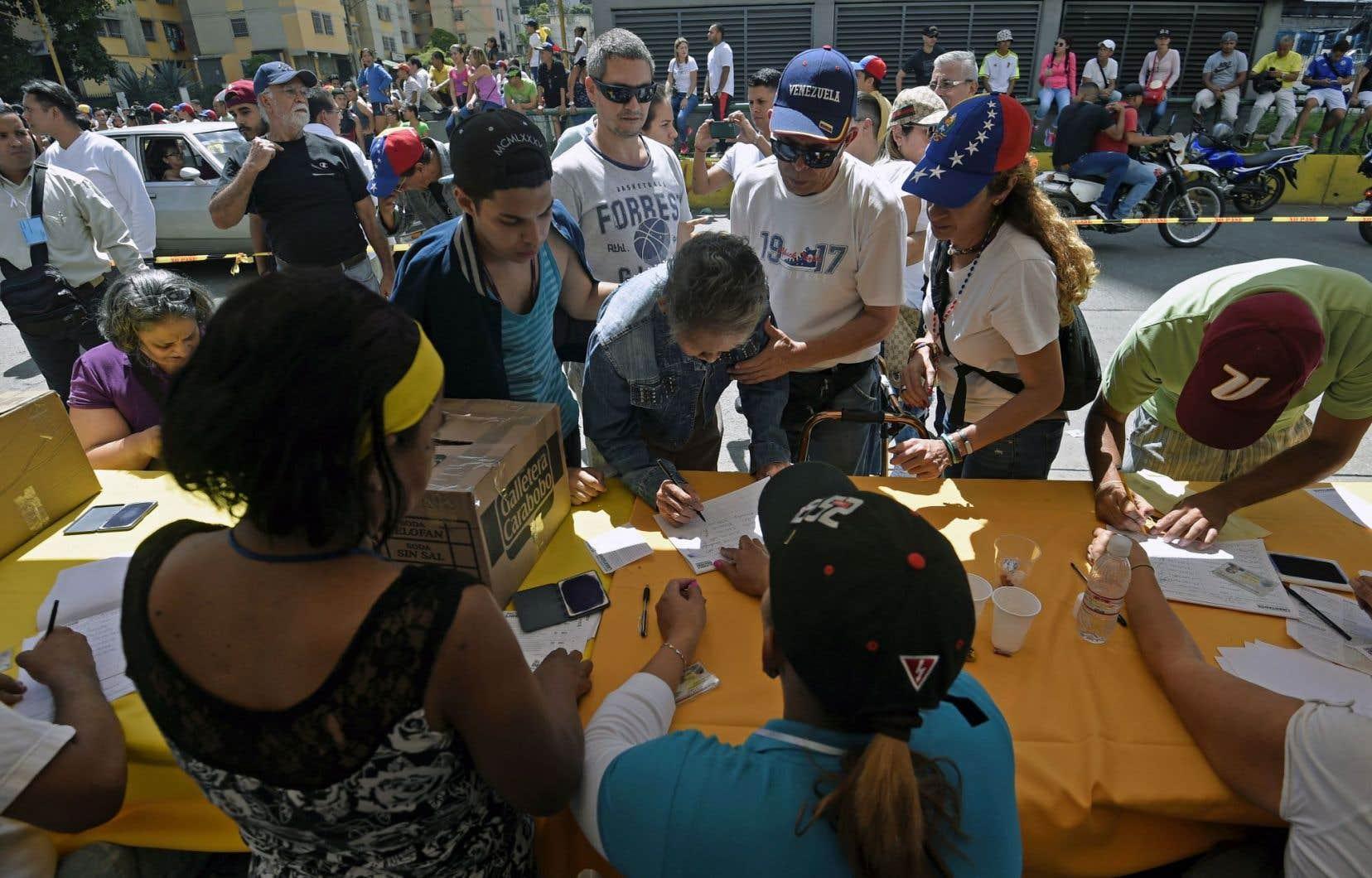 Par centaines de milliers, les électeurs vénézuéliens ont commencé dès dimanche matin à glisser leur bulletin dans des boîtes en carton installées dans des bureaux de vote à travers le pays par la coalition d'opposition, la Table de l'unité démocratique.