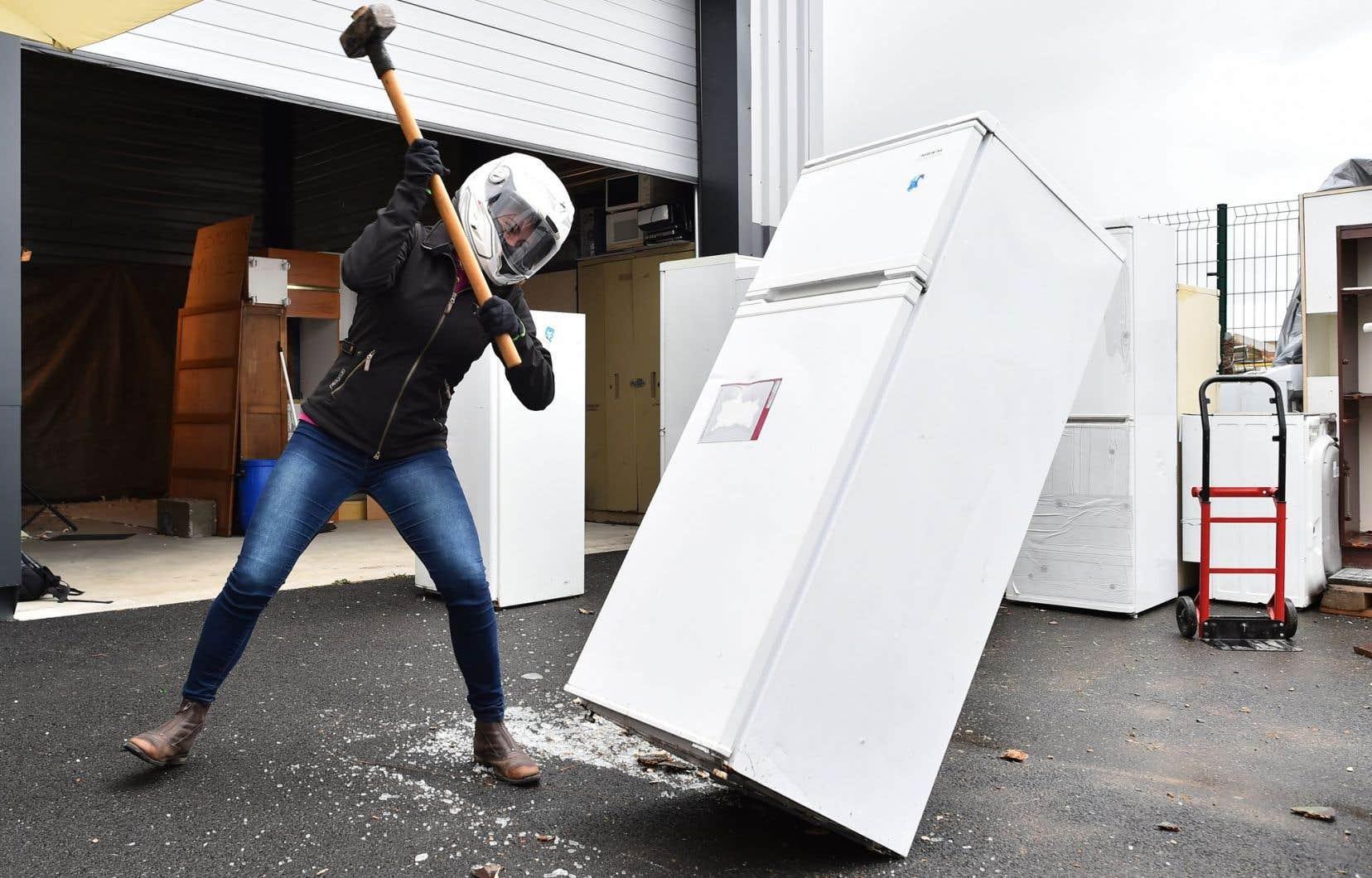 Une personne détruit un réfrigérateur avec une masse.