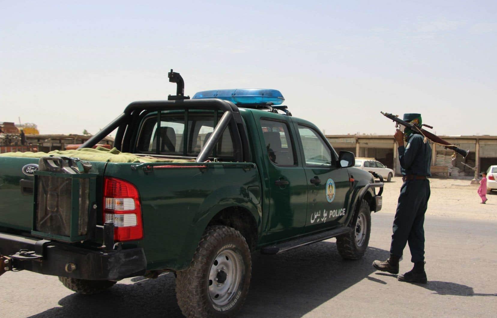 Un policier afghan détient une grenade propulsée par des roquettes (RPG) lors d'une bataille contre les militants talibans dans le district de Gereshk, au coeur de la province d'Helmand.
