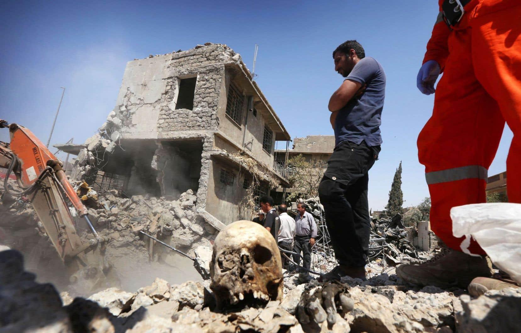 Les services de recherche fouillent les décombres de Mossoul à l'aide d'une pelle mécanique pour retrouver les corps des disparus.