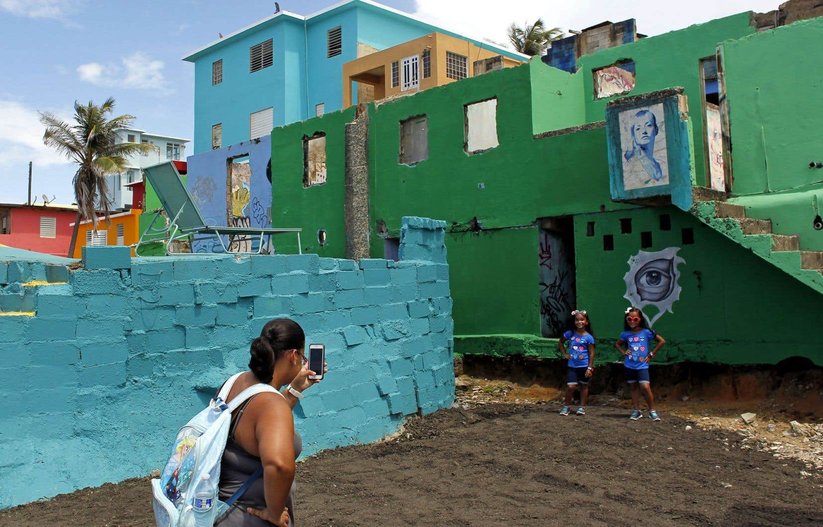 Une femme prend des photos de ses deux petites filles dans le quartier La Perla, où a été tournée la populaire vidéo <em>Despacito</em>.