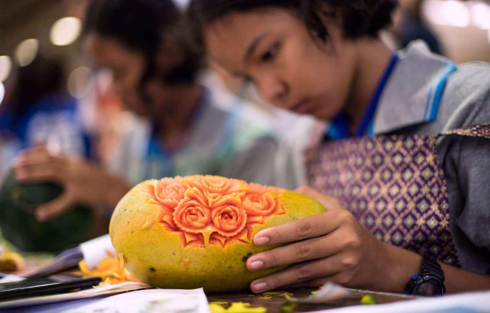 Une jeune Thaïlandaise sculpte des motifs floraux dans une papaye.