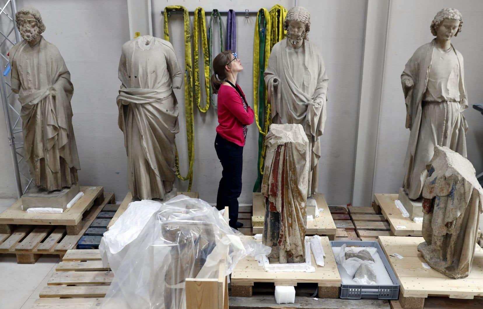 Alexandra Gérard, du Centre de recherche et de restauration des musées de France, observe les statues avec attention.