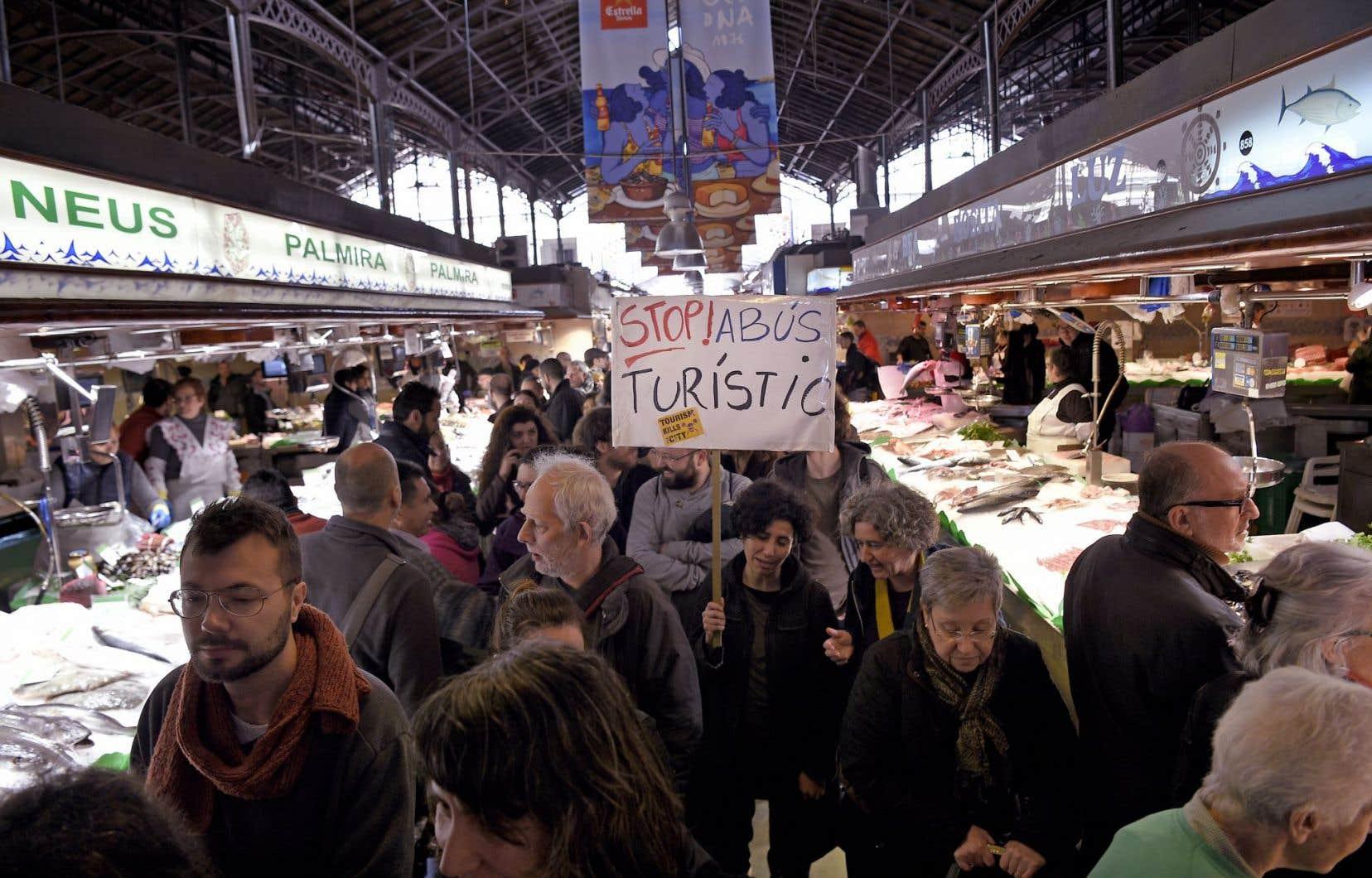 Une femme manifestait en janvier dernier au populaire marché La Boqueria de Barcelone. «Arrêtez les abus des touristes», réclame-t-elle.