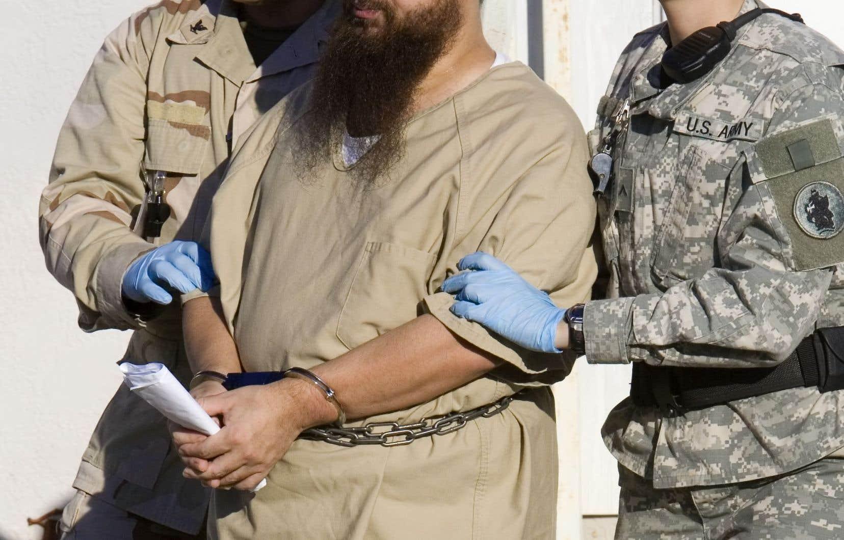 Un détenu est escorté par des gardes militaires vers son audience annuelle de la Commission d'examen administratif à la base navale américaine à Guantanamo Bay, Cuba. (2006)